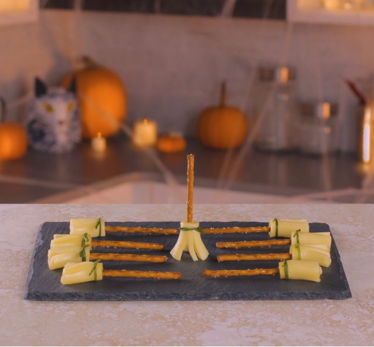 Nine fully assembled string cheese pretzel broomsticks displayed on a slate tray with fall decorations in the background.
