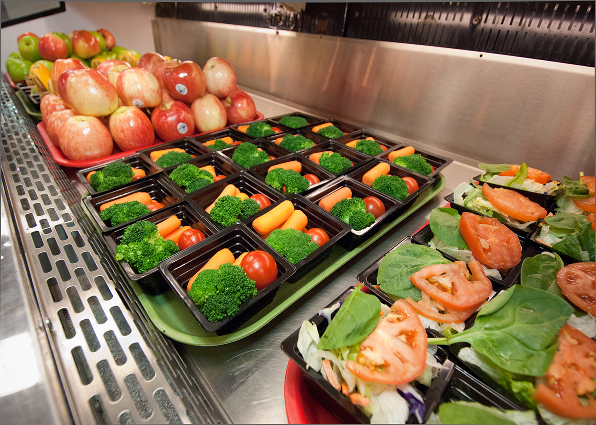 Prepared containers of colorful fresh fruits and vegetables lined up on a school lunch bar.