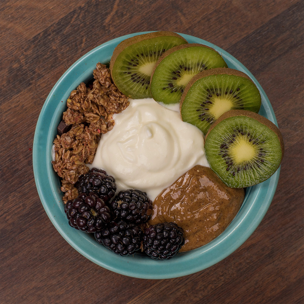 Bowl of yogurt topped with fresh fruit, granola and nut butter.