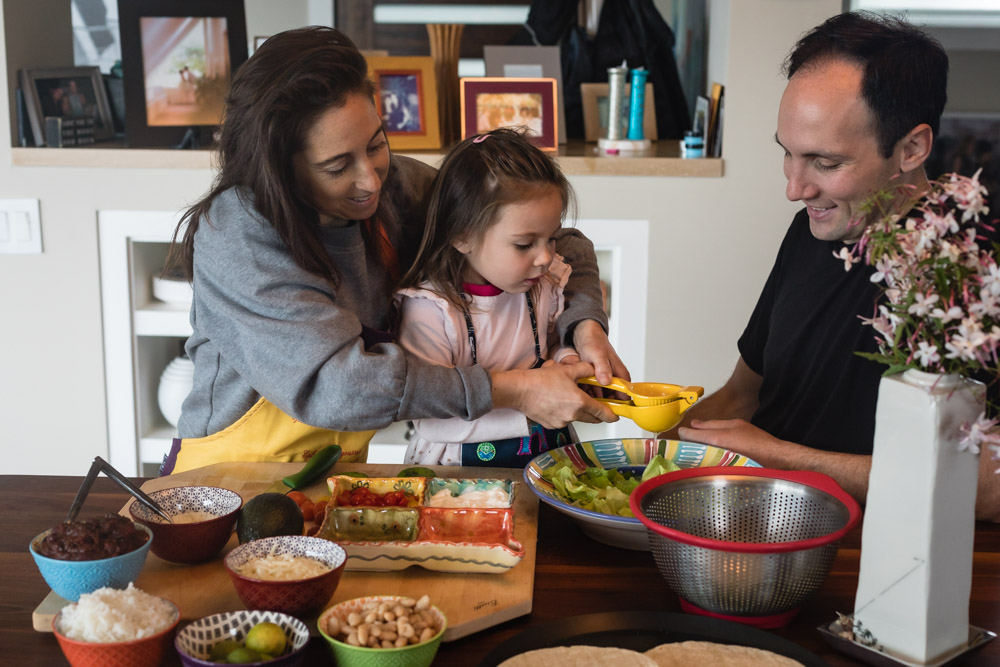 A mother, father and daughter prepare a taco spread together.