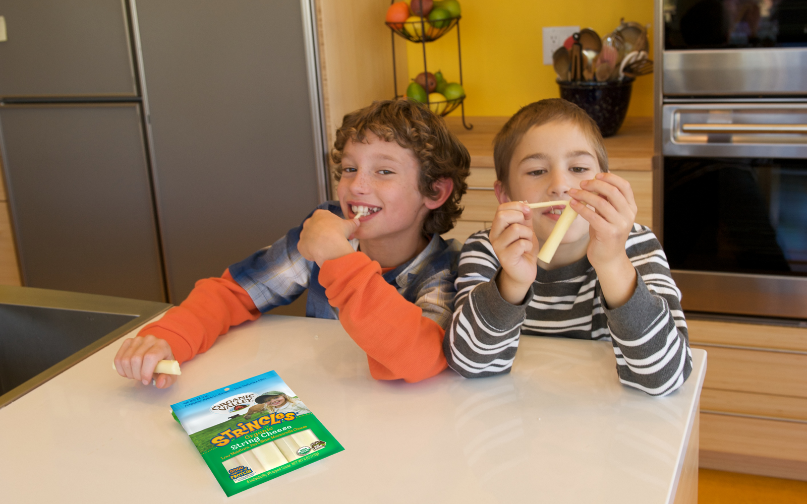 Two boys sitting at a kitchen counter, one smiling at the camera while taking a bite of cheese and the other peeling a stick of string cheese.