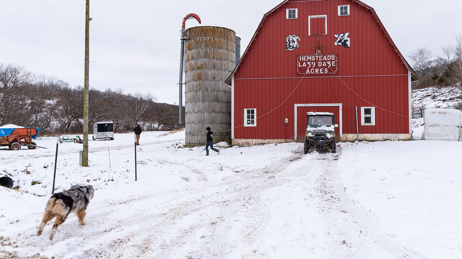 A farm dog runs through the snow to catch up to Kristina walking around the beautiful red milking parlor with a sign reading Lazy Daze Acres on the wall.