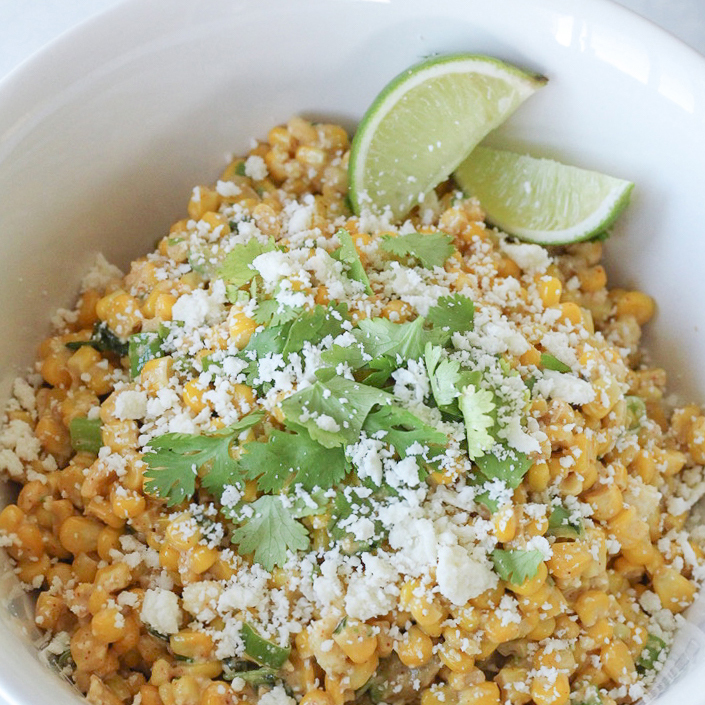 Fresh sweet corn off the cob made into a Mexican corn salad topped with fresh cheese cilantro and lime wedges.