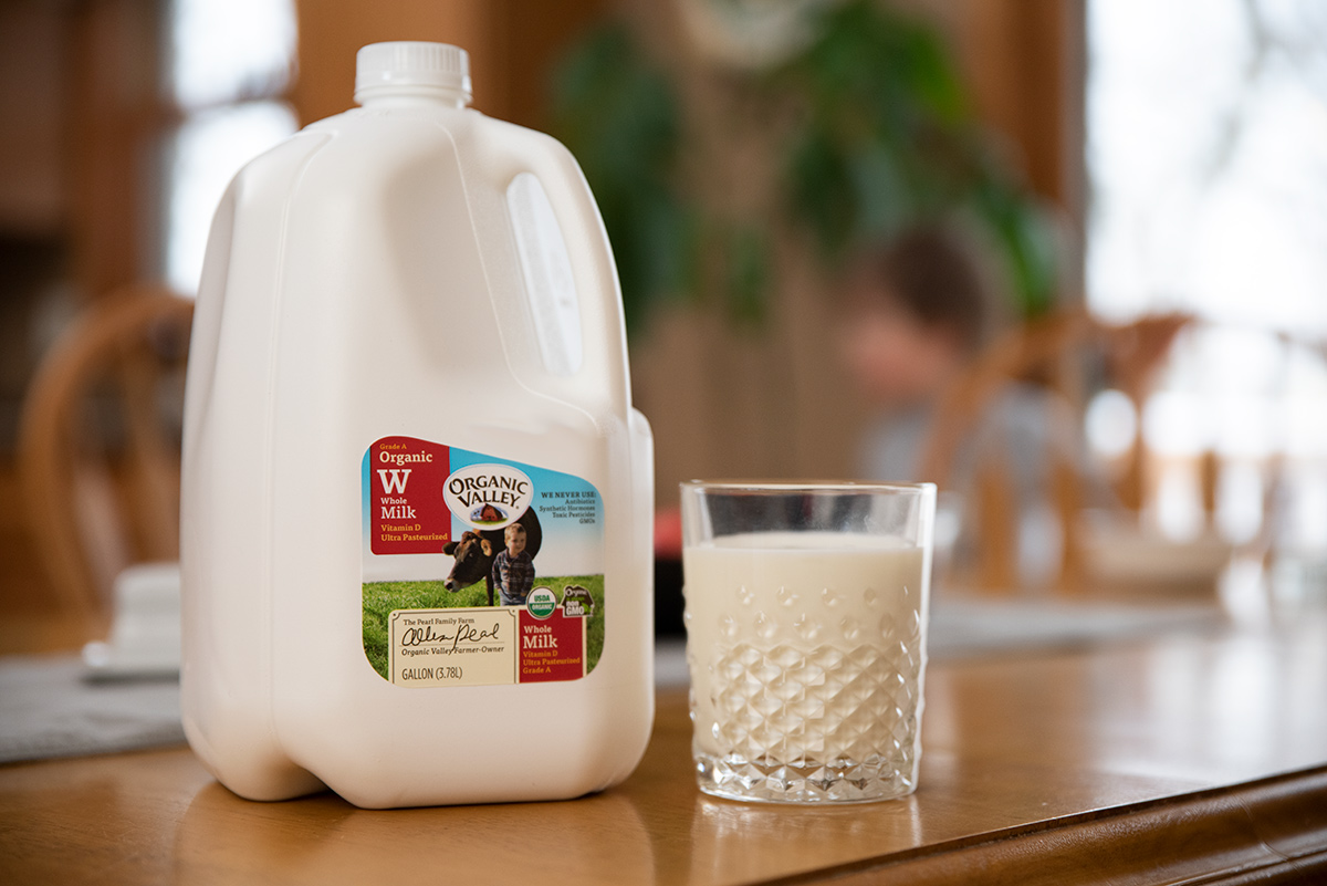 Gallon of Organic Valley whole milk sits on the kitchen table accompanied by a full glass.