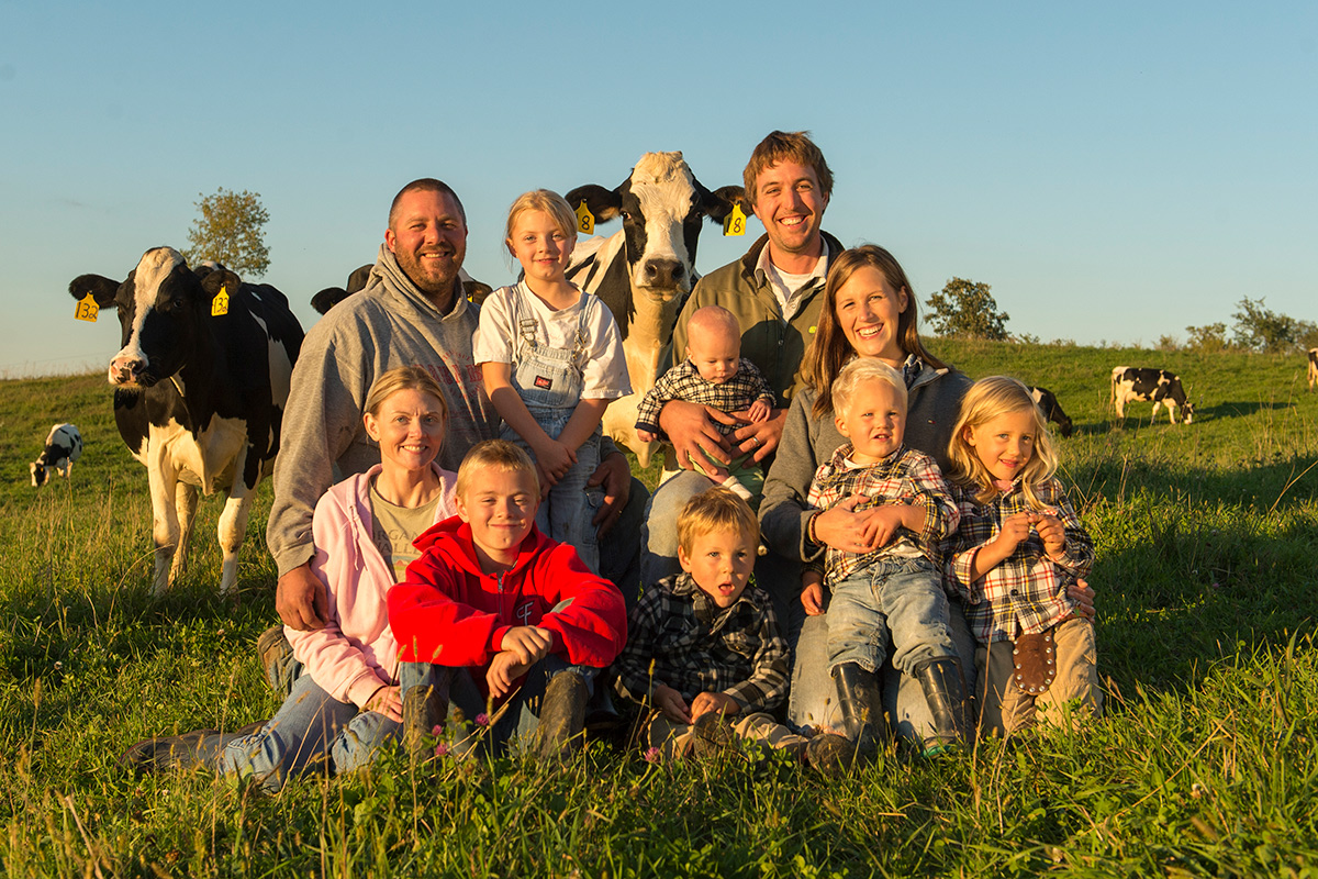 The O'Reilly family pose in a green pasture with cows and blue sky in the background.