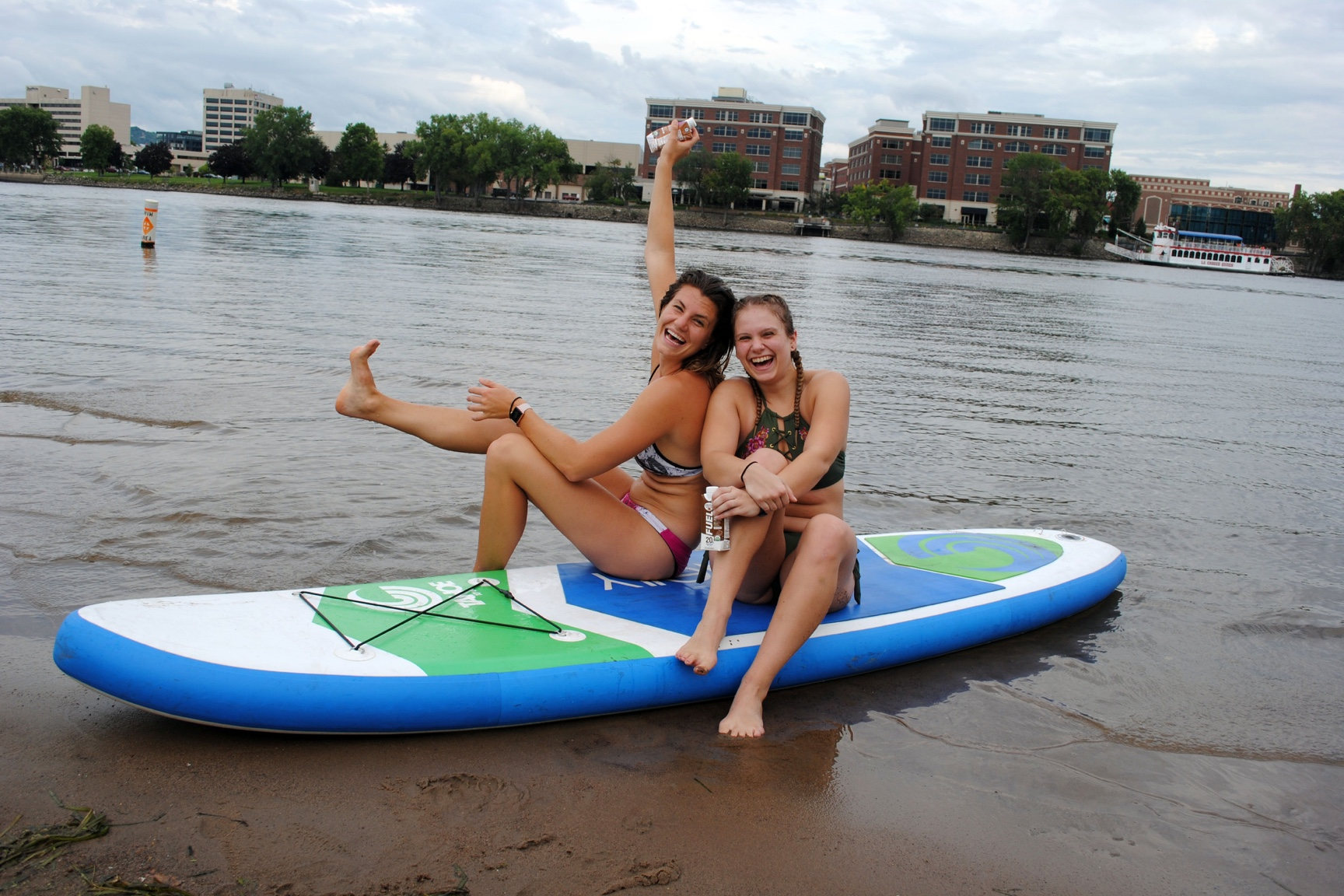 The author and a friend laugh and strike a funny pose while holding Organic Fuel and sitting on a paddle board on a river.