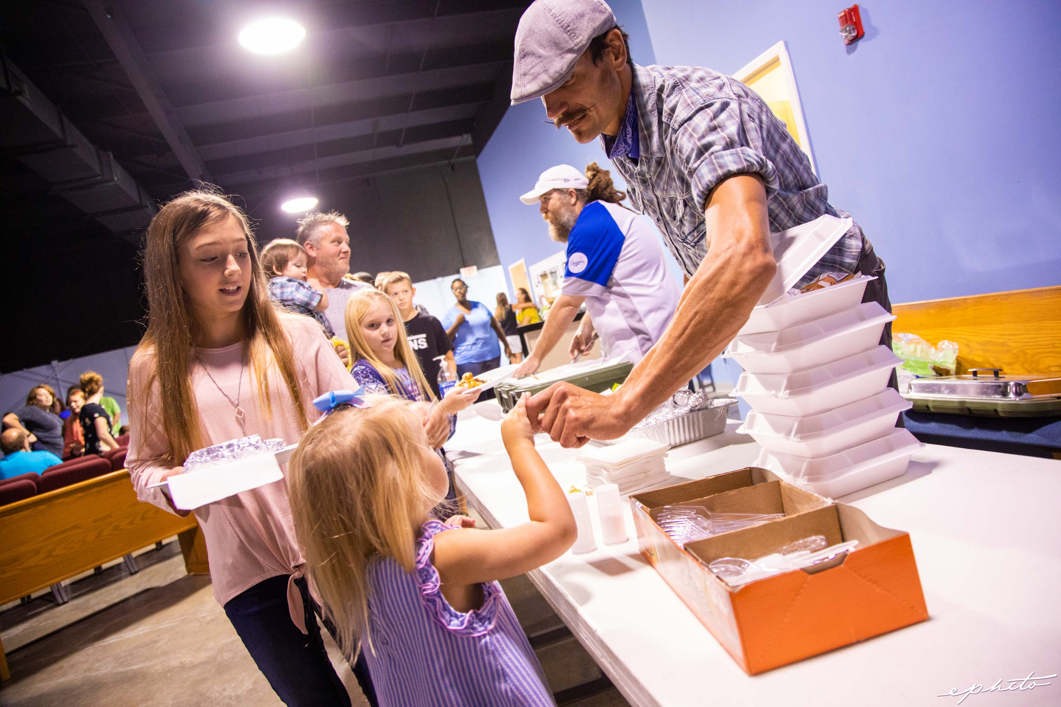 A little girl takes a utensil from a male volunteer in a disaster relief foodservice line.