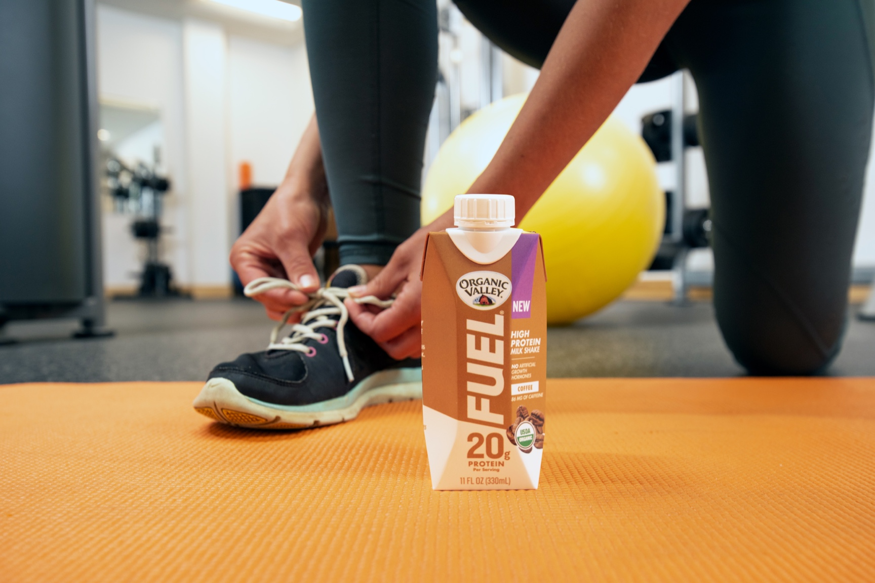 A woman in a gym ties her shoe with a carton of Organic Valley Fuel beside her.
