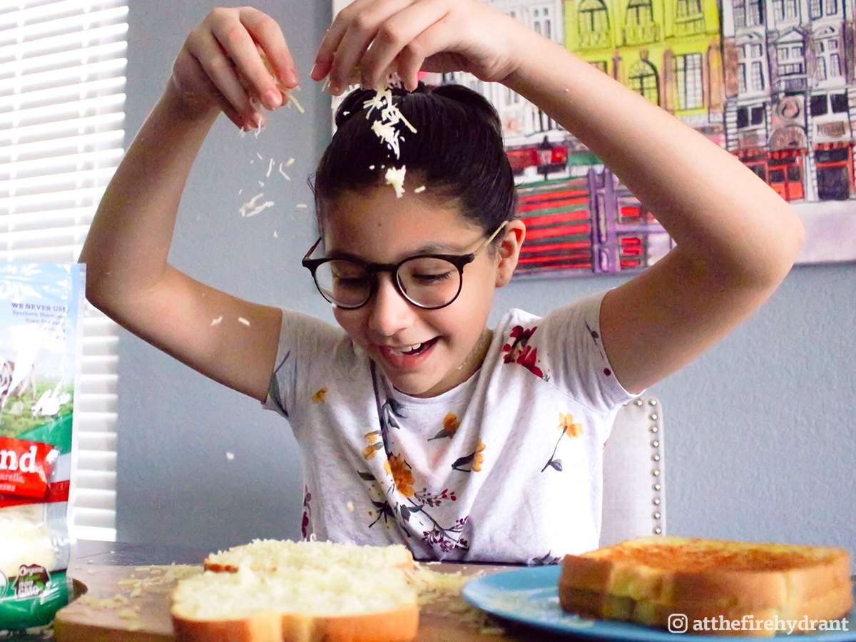 Preteen girl in glasses puts together a grilled cheese sandwich.