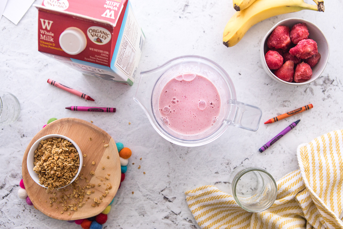 Overhead view of a smoothie in a cup surrounded by an Organic Valley milk carton, frozen strawberries, granola, and crayons for decor.