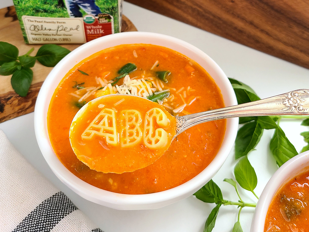 A spoon holds A, B, C pasta over a bowl of tomato-based soup sprinkled with shredded cheese.