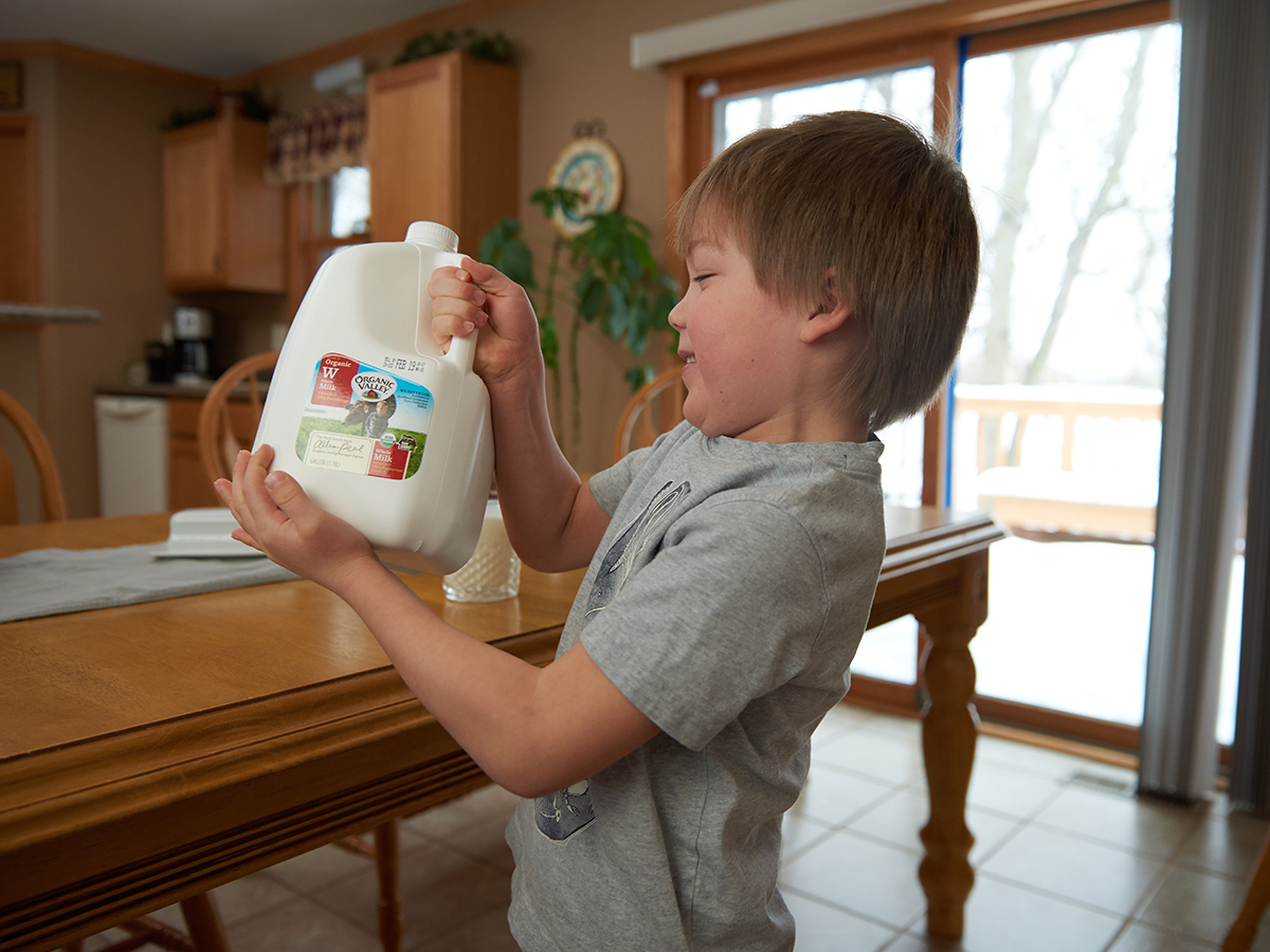Young boy holds a gallon of Organic Valley milk and brings it to the table.