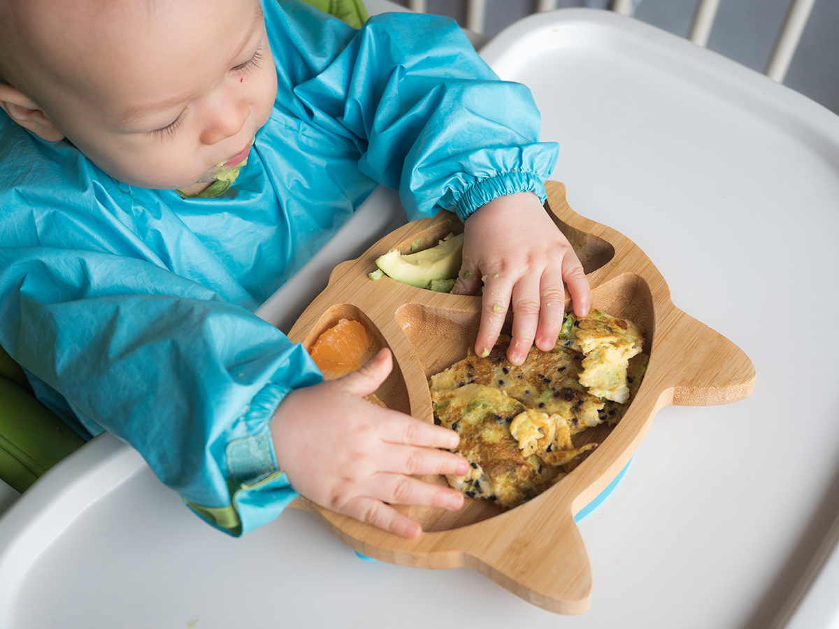 Asian baby eats a plate of food, including avocados and scrambled eggs.