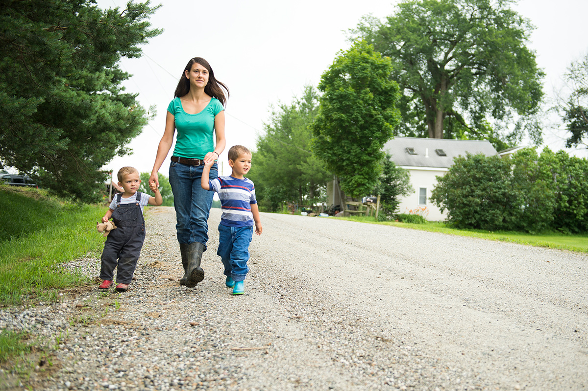 Emily Donegan hold her sons' hands while walking around the farm in Vermont.