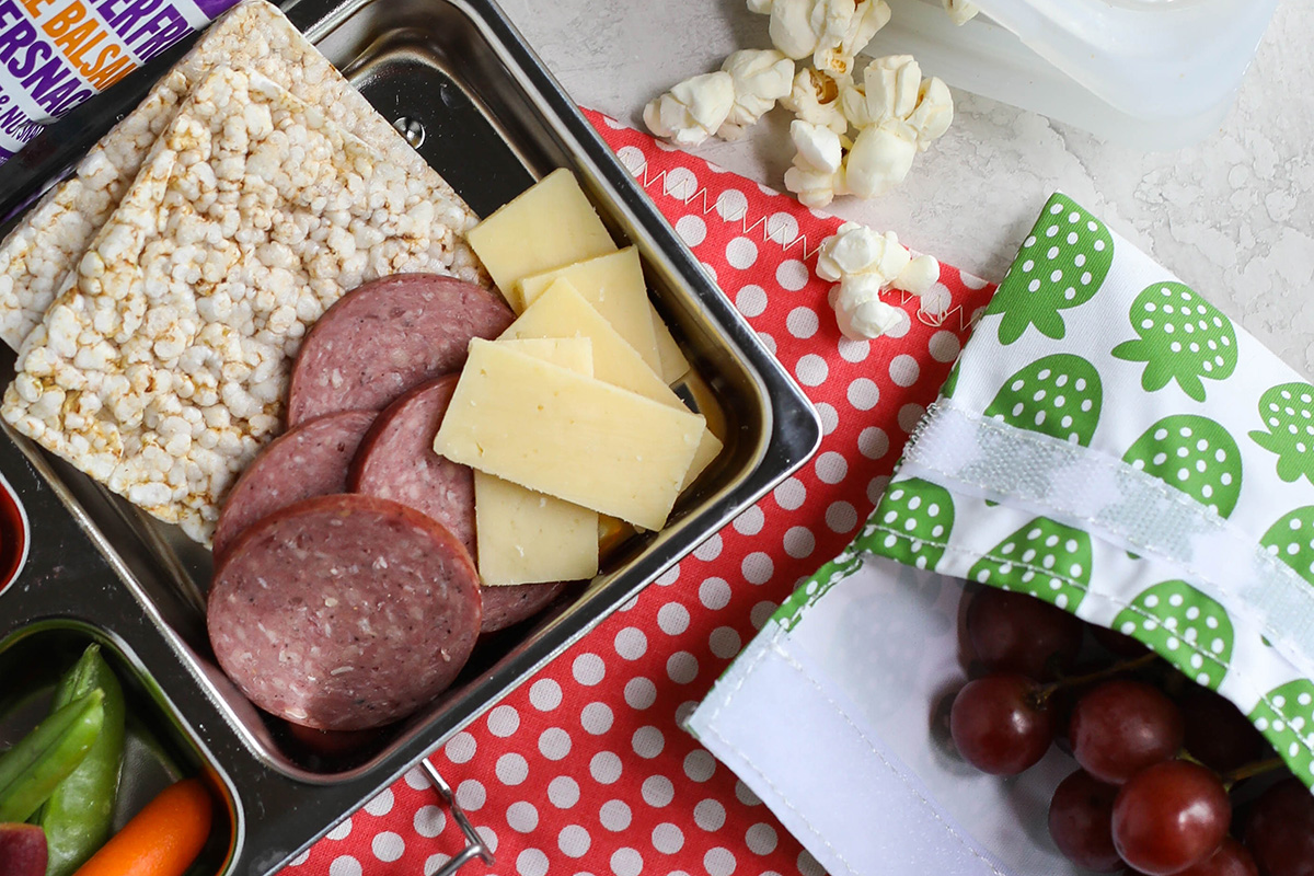 A packed lunchbox with organic summer sausage and other snacks.