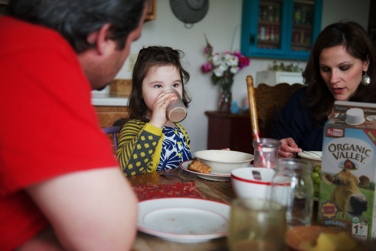 A family is eating at the dinner table, and a little girl is drinking chocolate milk.
