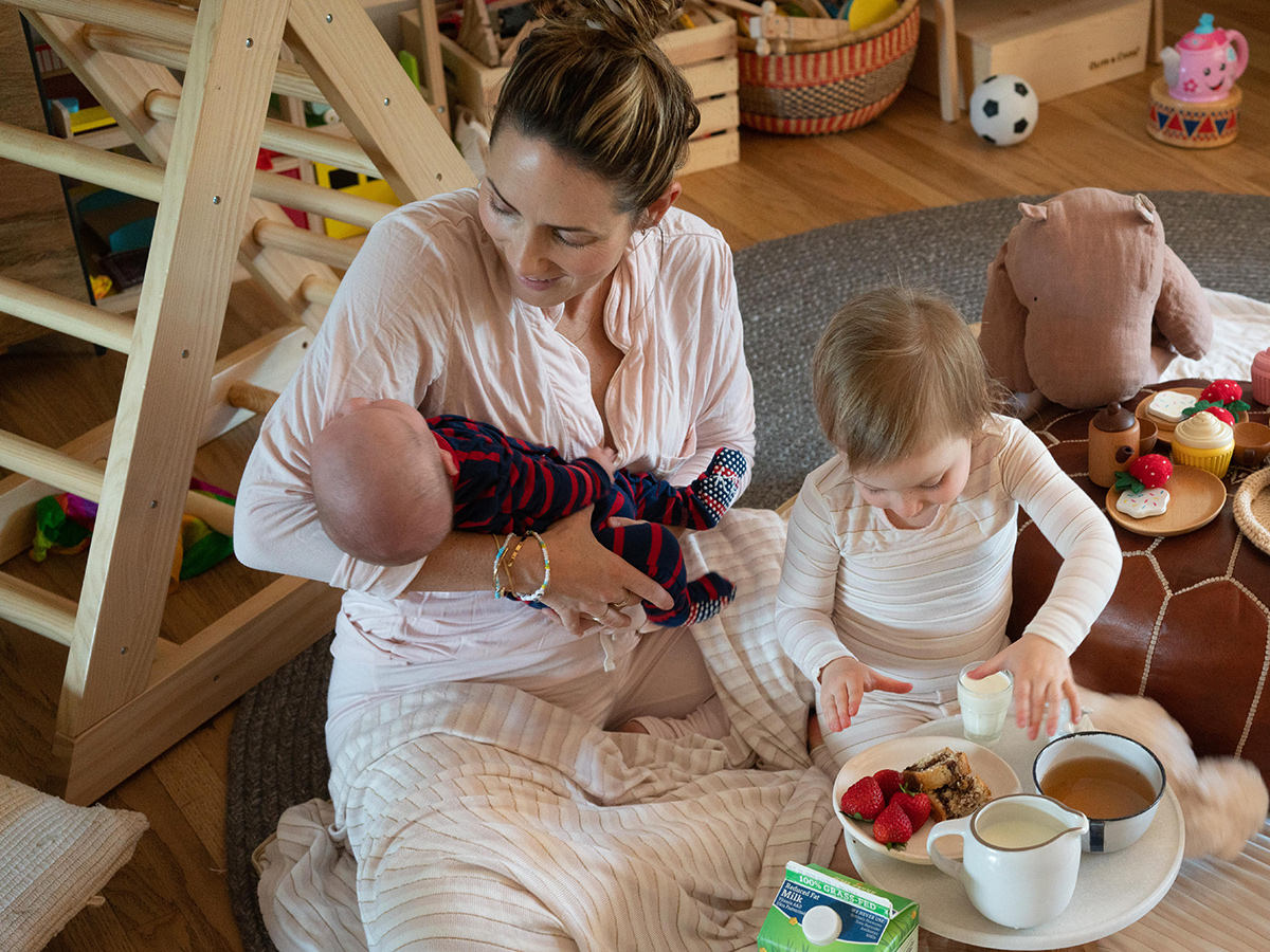 Young mom holds her baby while her daughter has a tea party nearby.
