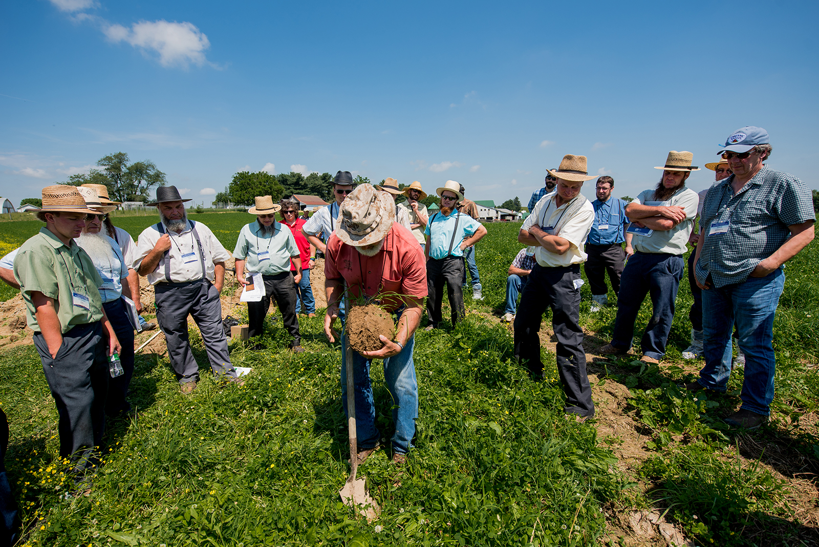 Organic Valley farmers gather around Soil Agronomist Mark Kopecky on a blue-sky day at a soil and pasture workshop in Ohio.