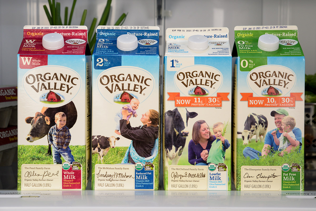 Organic Valley Milk products with open refrigerator in background.