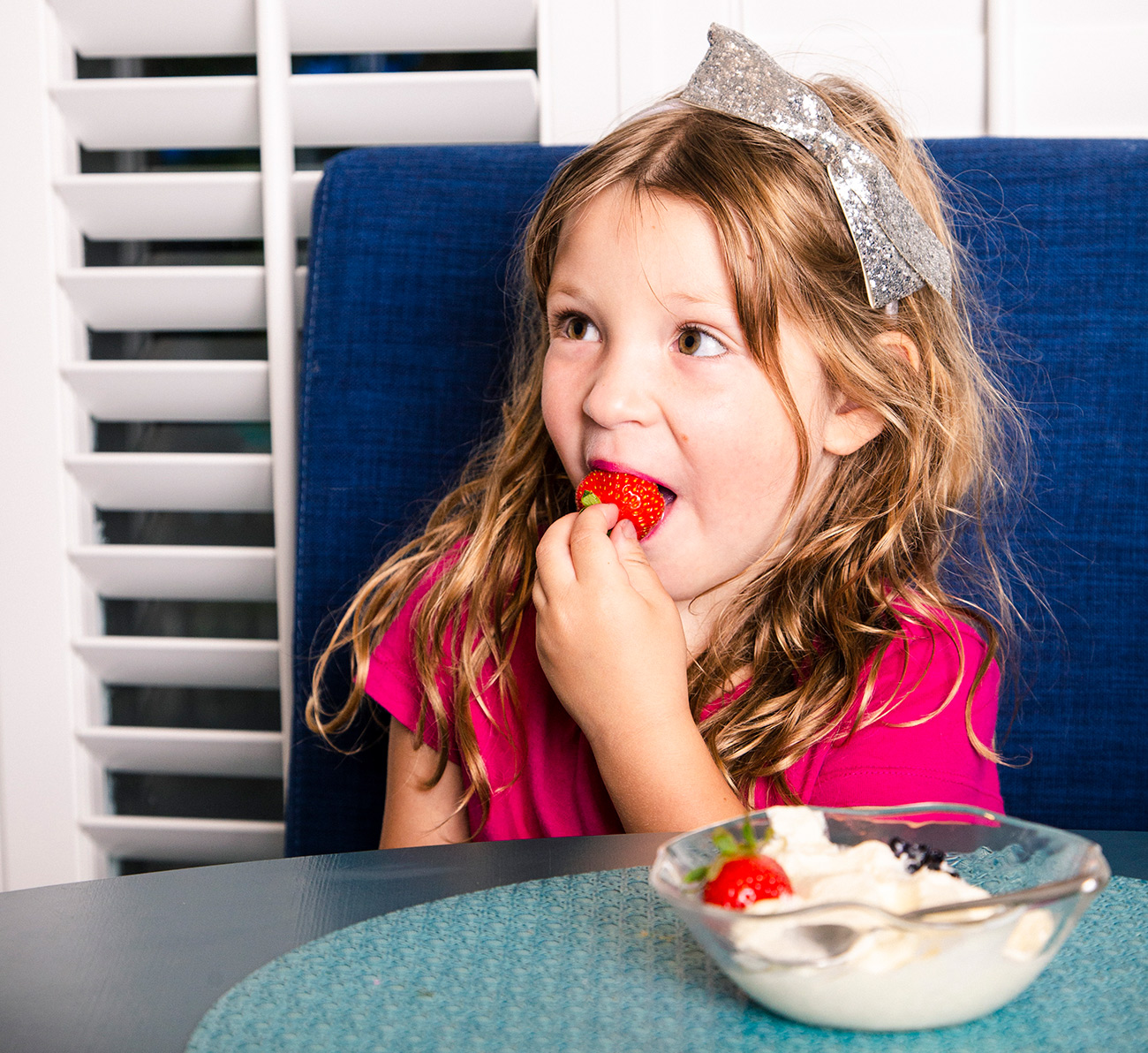 A young girl wearing a pink shirt eats a strawberry with whipped cream.