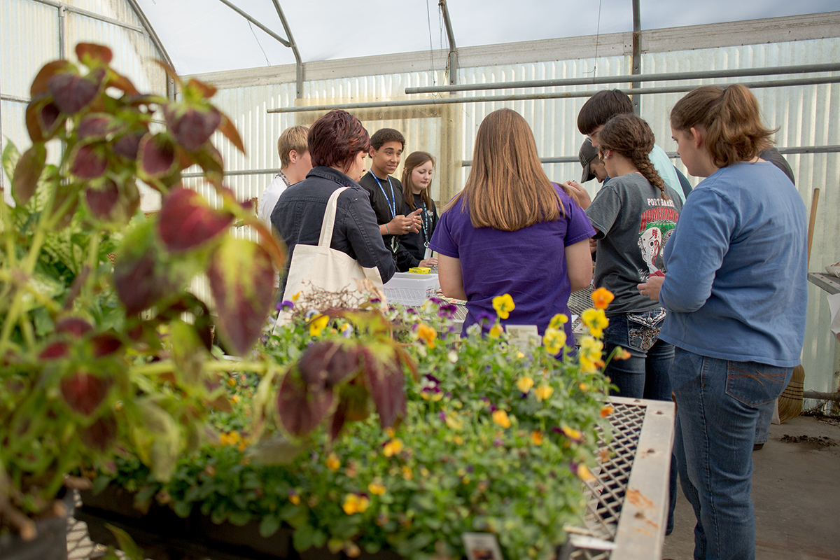 Group of teachers and students gather in a school greenhouse to learn about school gardens.