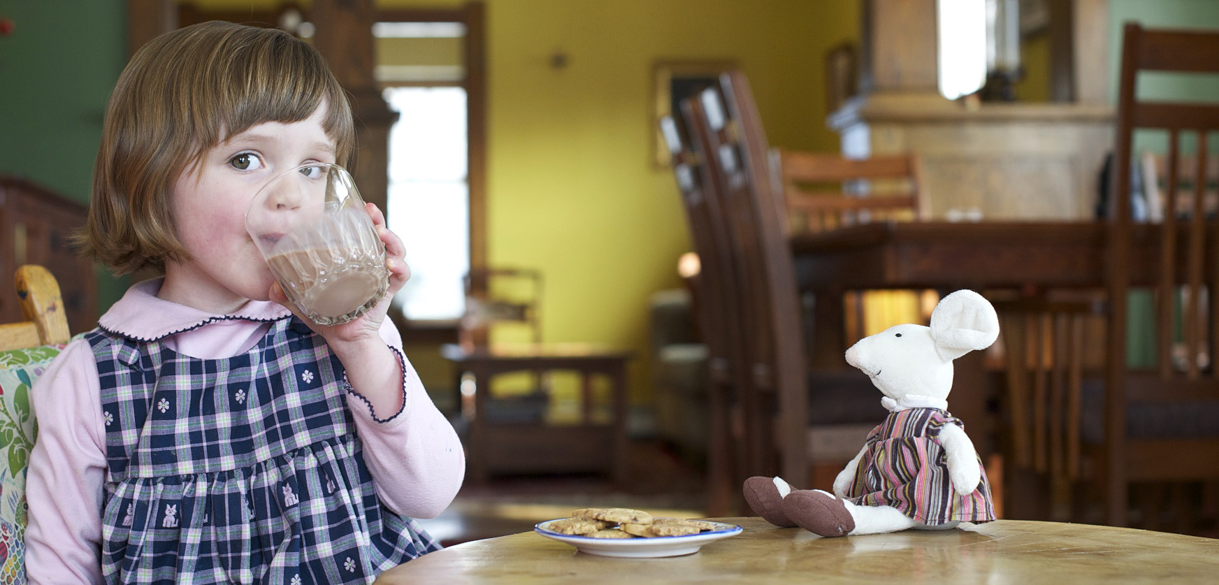 A young girl drinks chocolate milk with a plate of cookies and her toy mouse on the table in front of her.