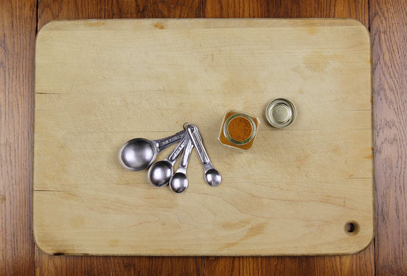Turmeric powder with measuring spoons on a cutting board.