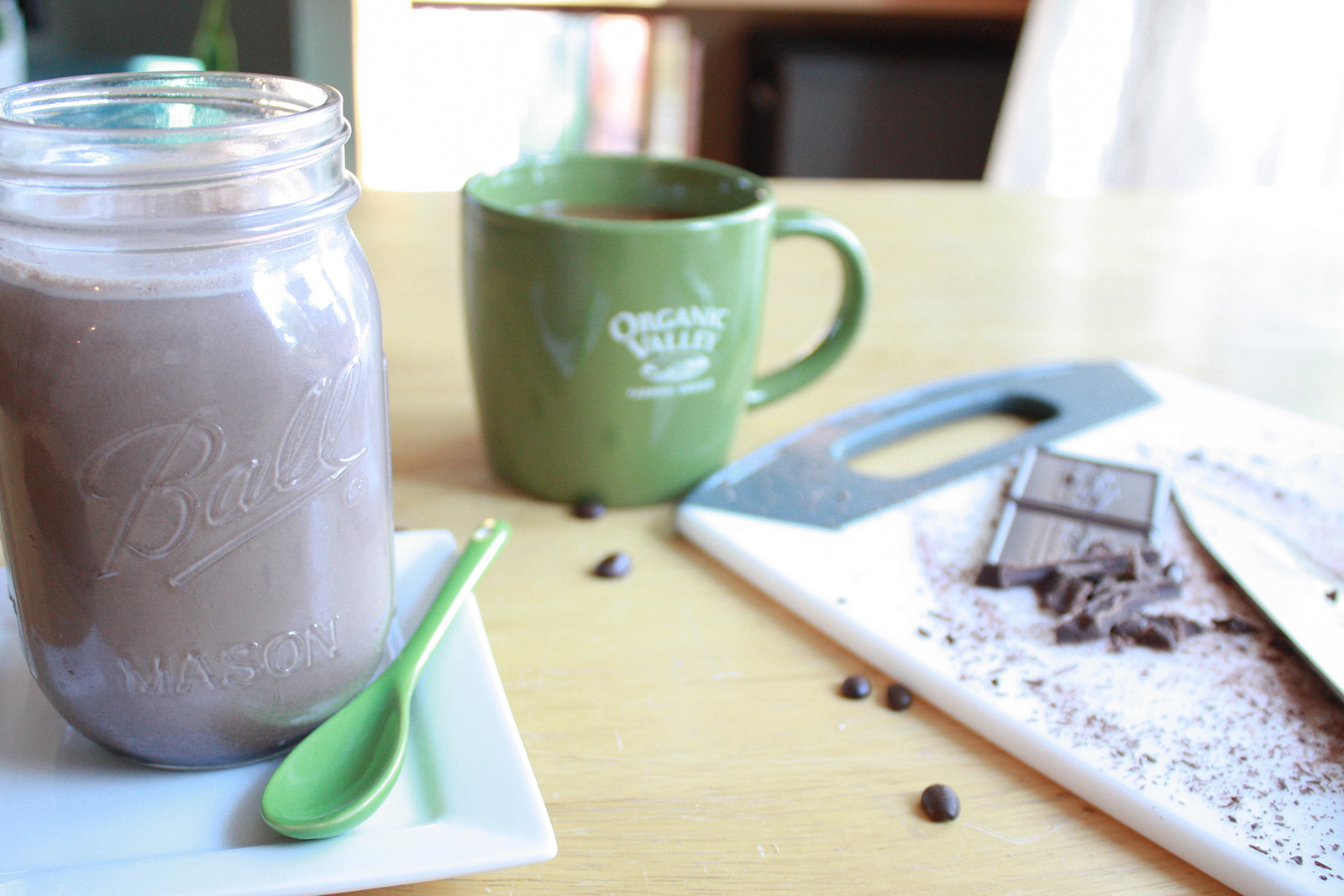 Homemade peppermint mocha coffee creamer in mason jar and green mug.