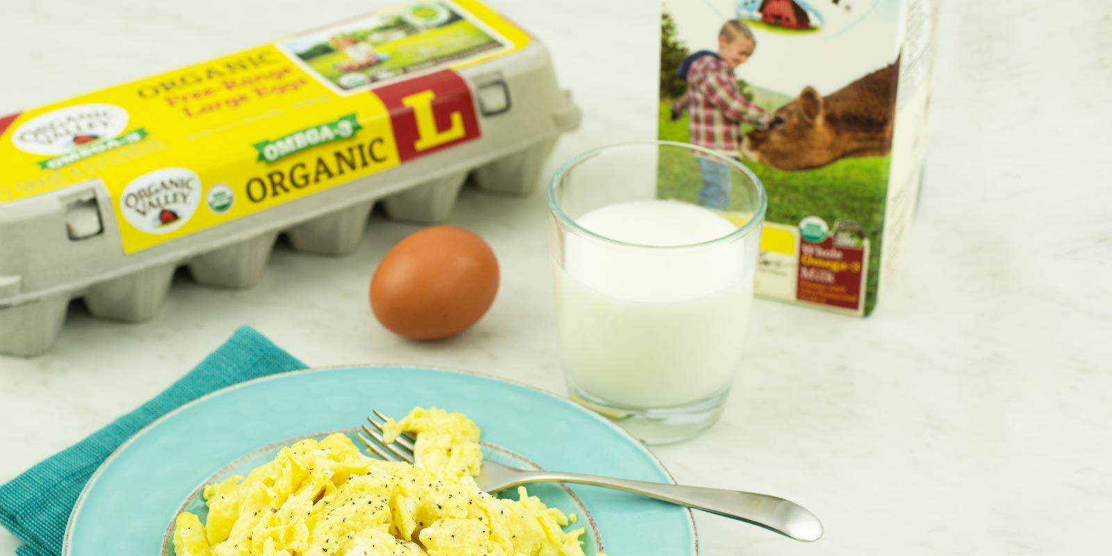 A plate of yellow scrambled eggs next to a glass of milk and a whole egg, all in front of a carton of Organic Valley Omega-3 Eggs and a carton of Organic Valley Omega-3 Milk.