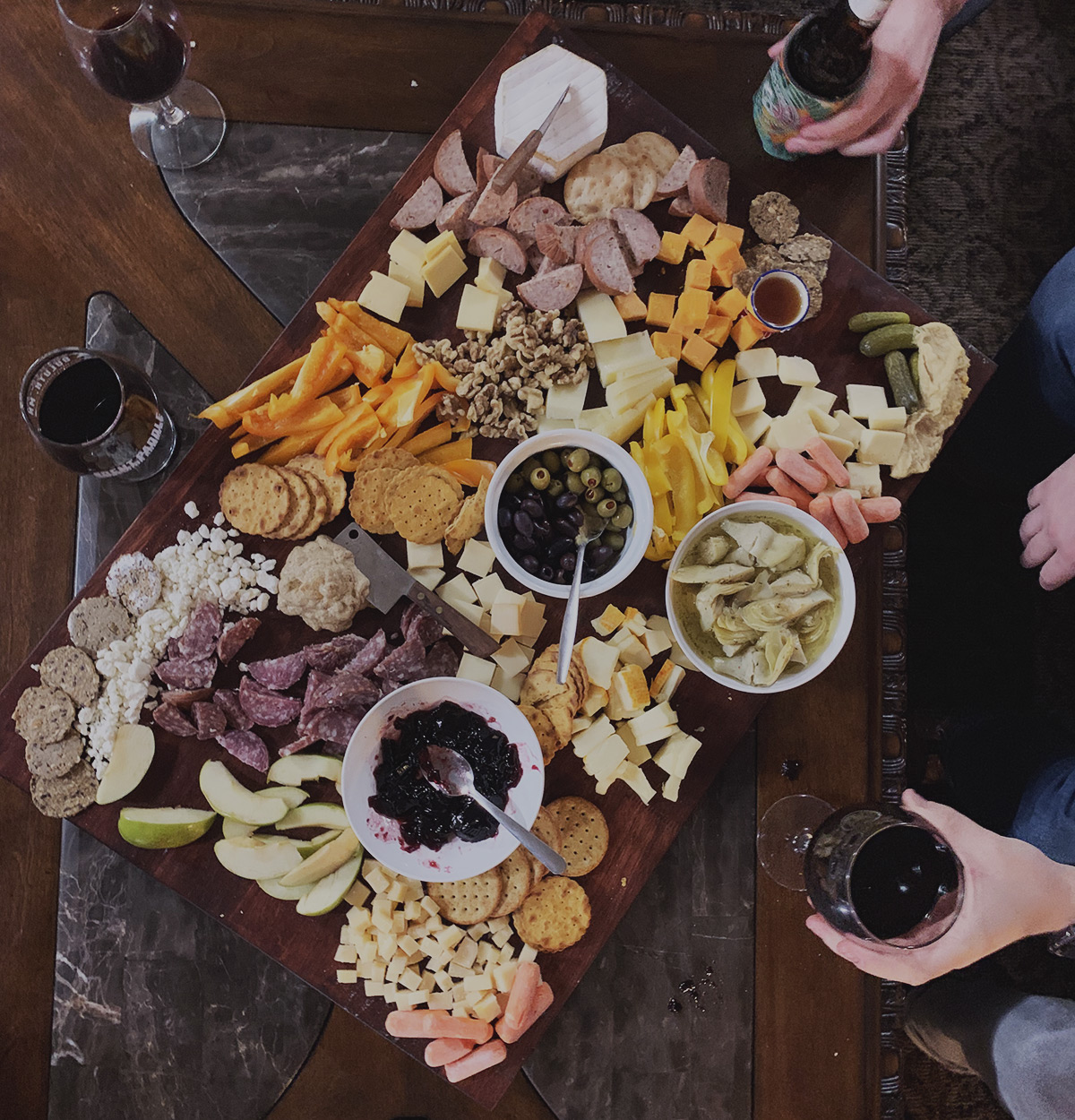 Overhead shot of a scrumptious charcuterie board with drinks in hand.