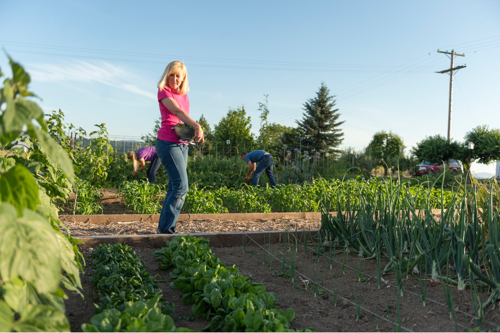 Juli Bansen overlooks her bountiful farm garden of spinach, onions, and more while her children weed in the background.