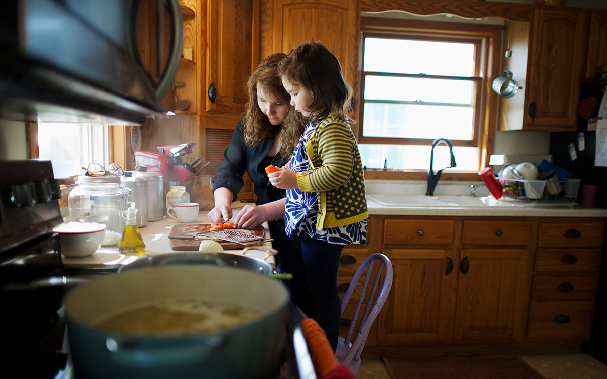 A young girl stands on a chair at the kitchen counter and watches her sister chop carrots. A pot of soup simmers on the stove.