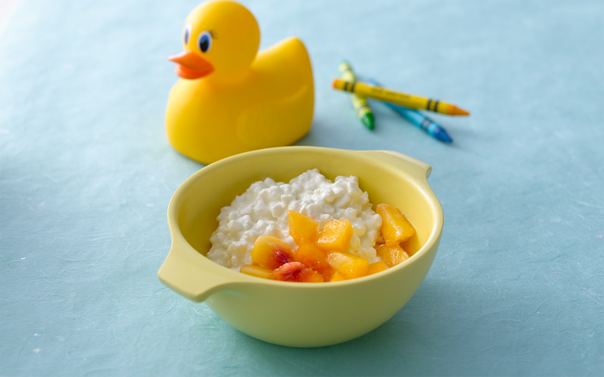 A cup of cottage cheese and cut peaches with a rubber ducky and some crayons in the background.