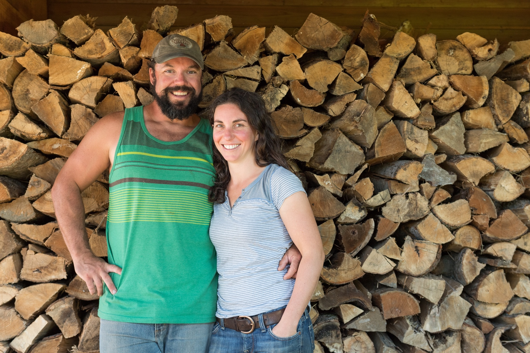 Tyler and Melanie smile at the camera while standing in front of a large stack of firewood.