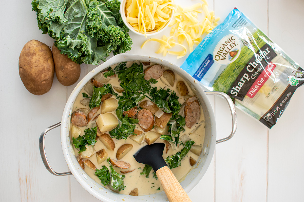 Creamy sausage potato and kale soup with thick-cut sausage, potato chunks, and wilted kale topped with shredded cheese.
