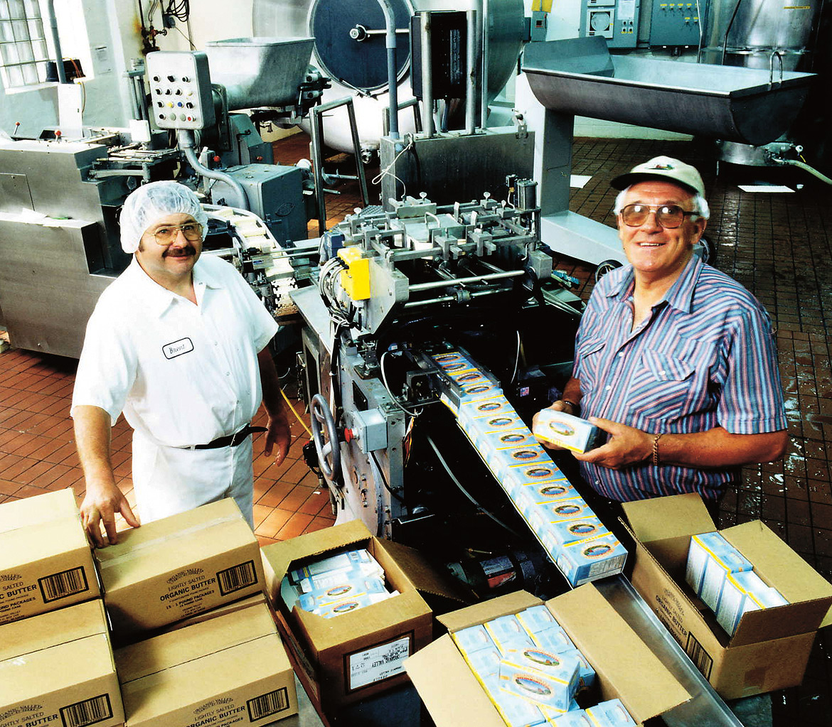 Two men stand in the creamery next to a butter packaging machine and many partially filled shipping boxes.