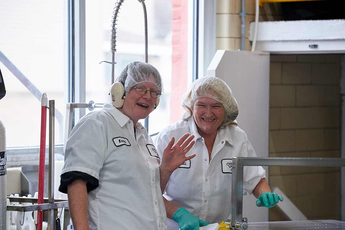 Two women in an Organic Valley production facility wearing white overcoats, hair nets and gloves smile and wave at the camera.