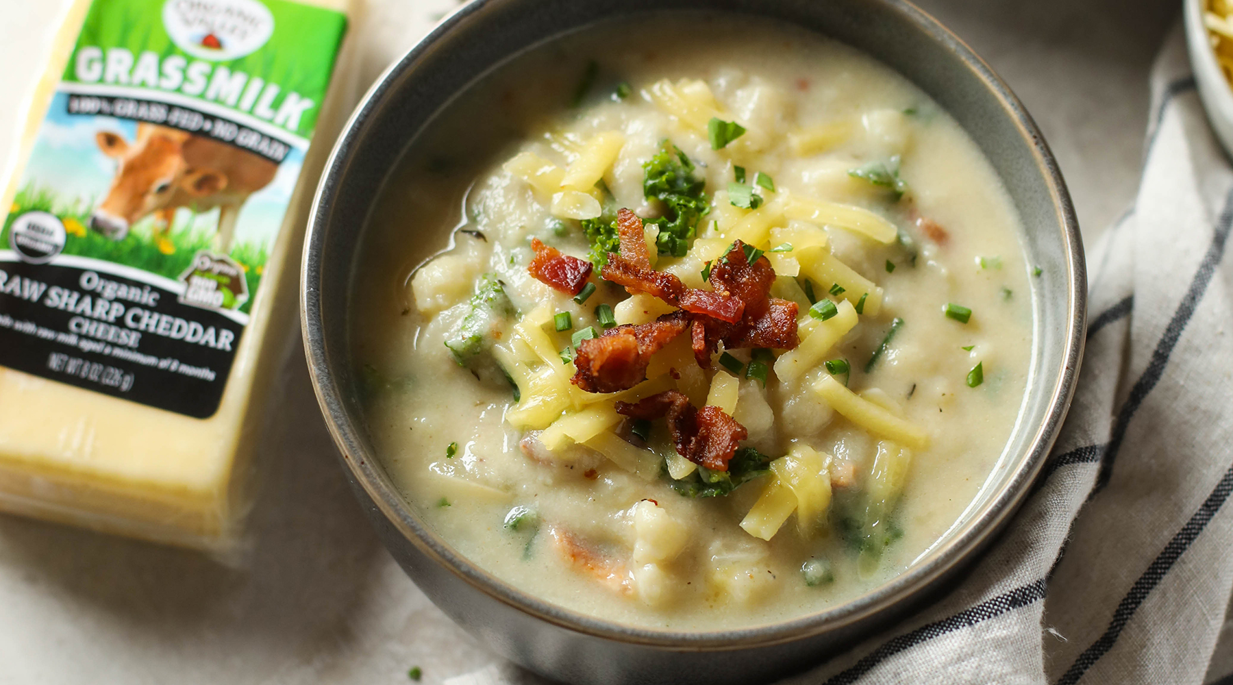 A bowl of Loaded Cheesy Cauliflower Soup using Organic Valley's Grassmilk Cheddar, topped with bacon crumbles. Image credit: the Real Food Dietitians.