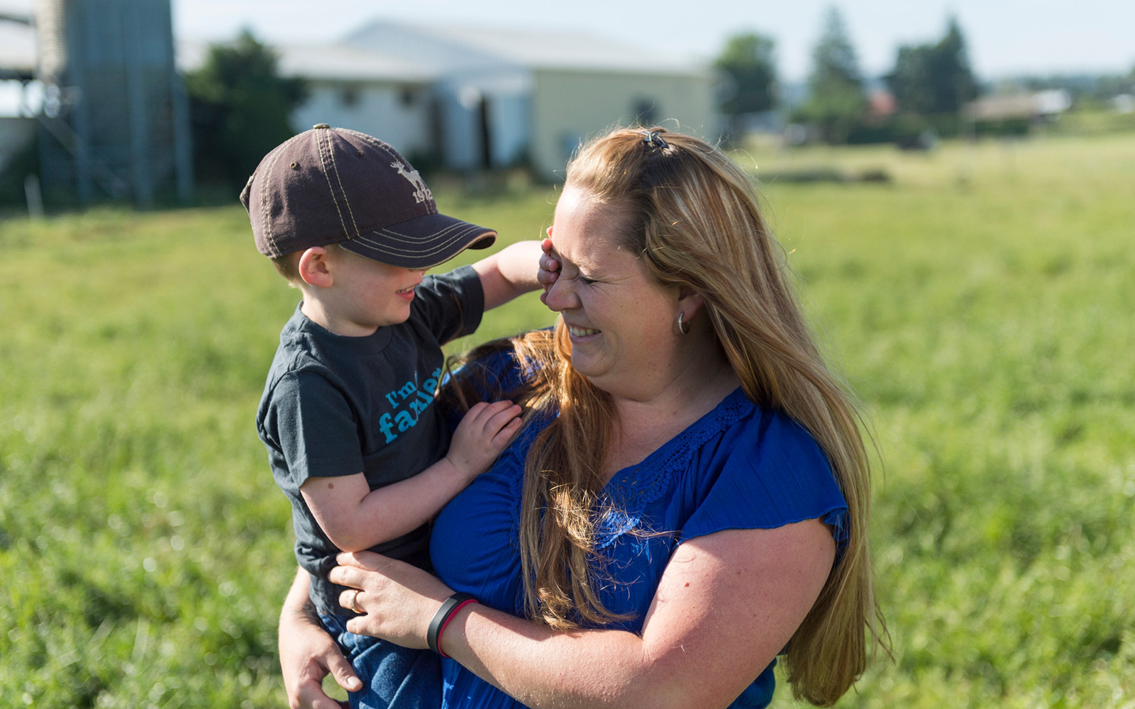 Melissa Collman laughs as her son covers one of her eyes with his hand.