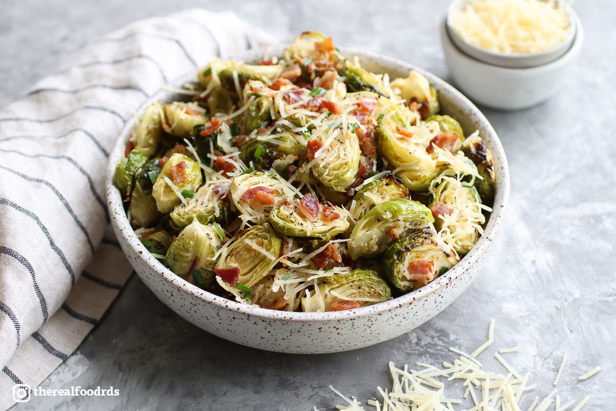 A bowl of roasted Brussels sprouts artfully garnished with shredded cheese and bacon crumbles.