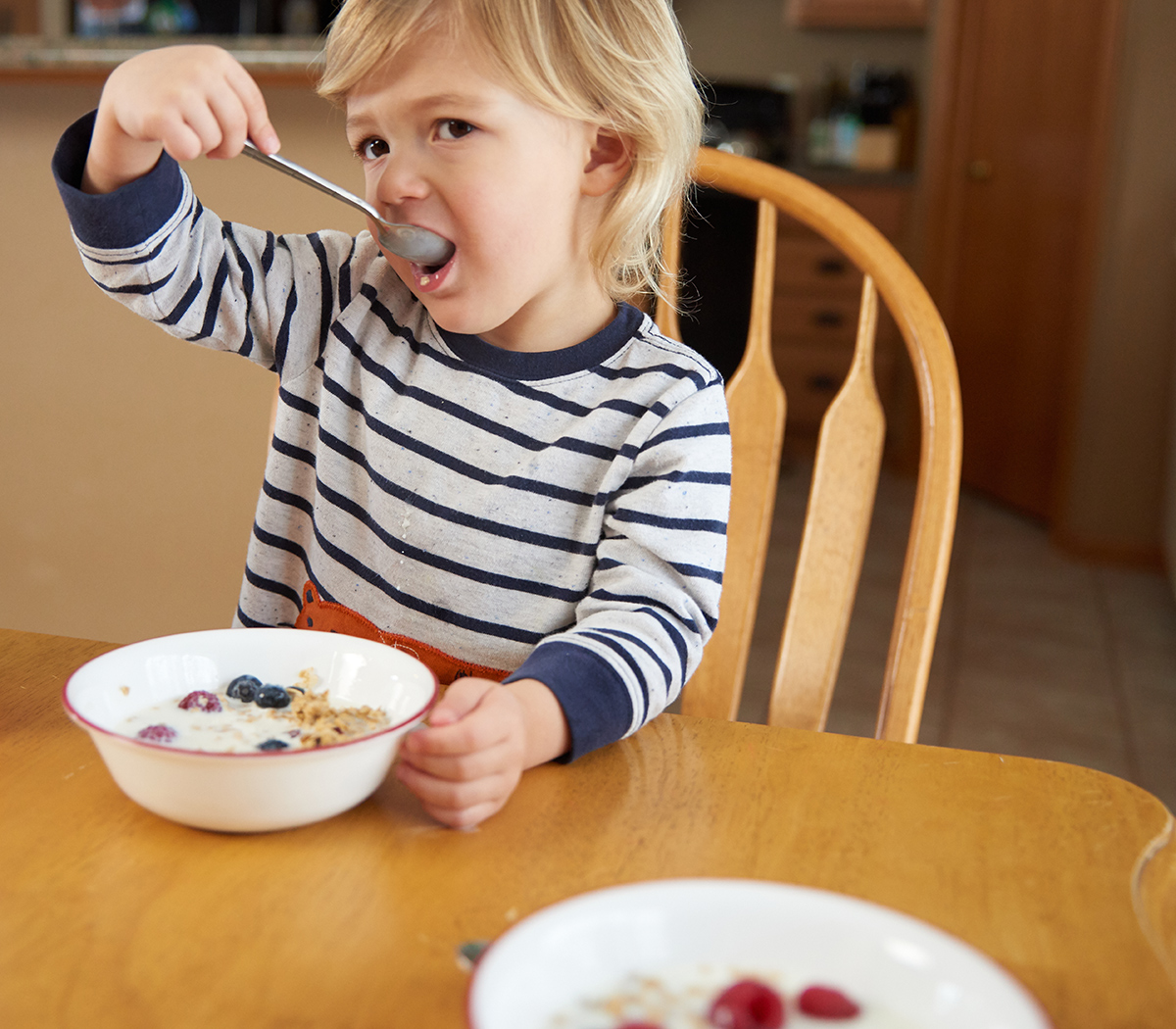 A little boy eats a bowl of cereal topped with fresh berries.