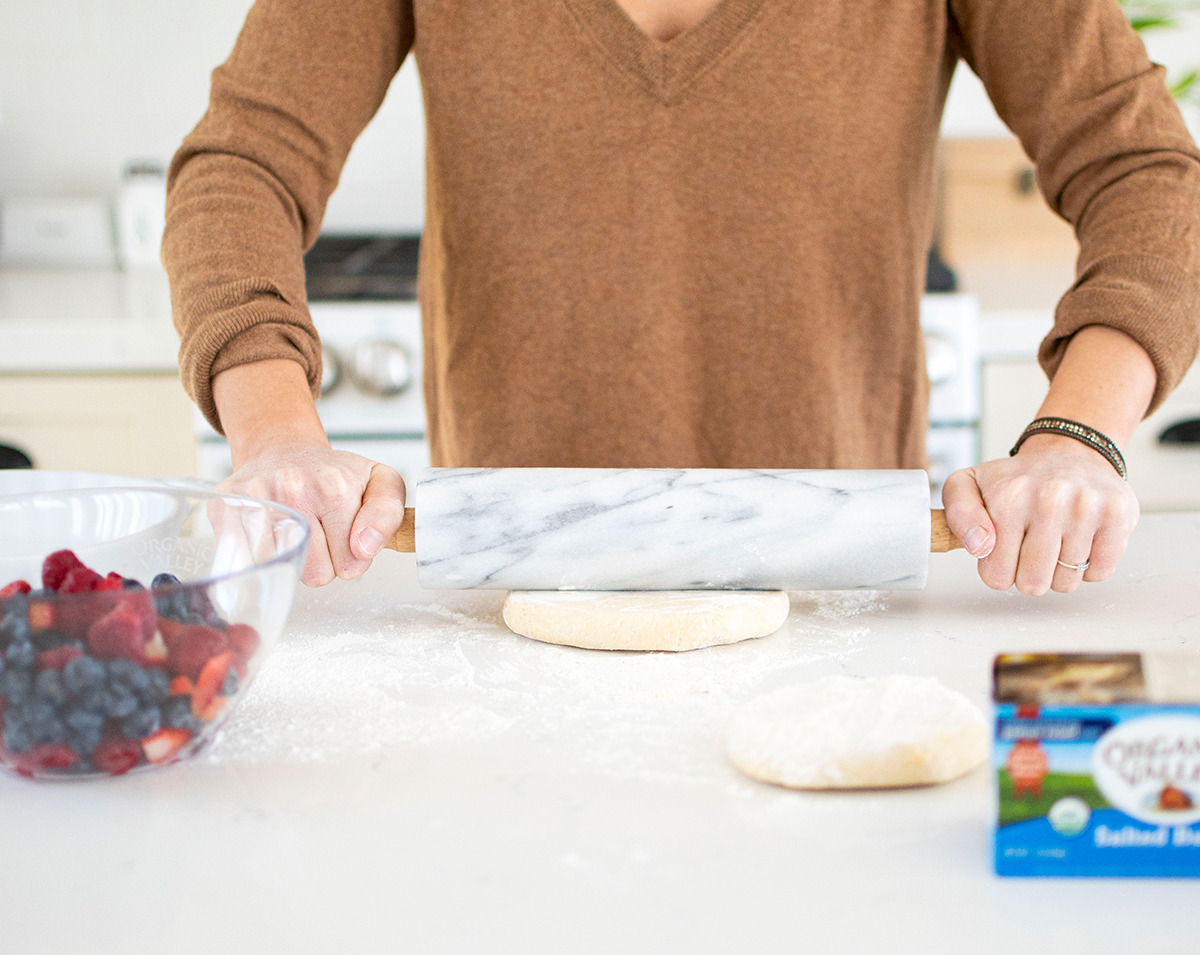 Woman rolling out pie dough on a counter.