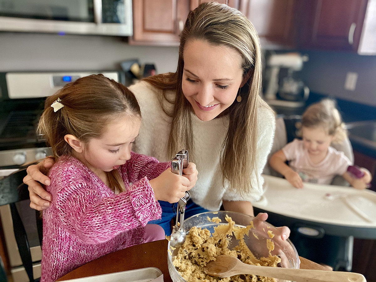 A mother smiles while her daughter wearing a pink sweater scoops cookie dough out of a bowl.