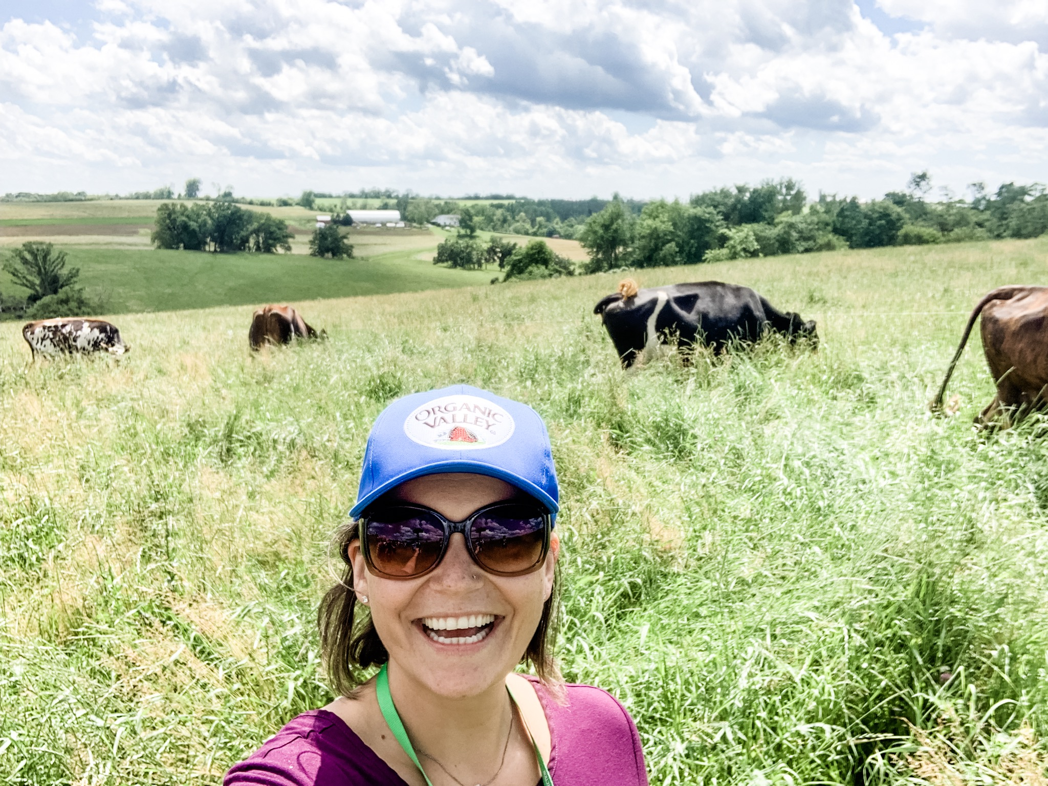 Carolina, wearing a blue Organic Valley hat and sunglasses, takes a selfie in front of grazing cows and a rolling landscape.