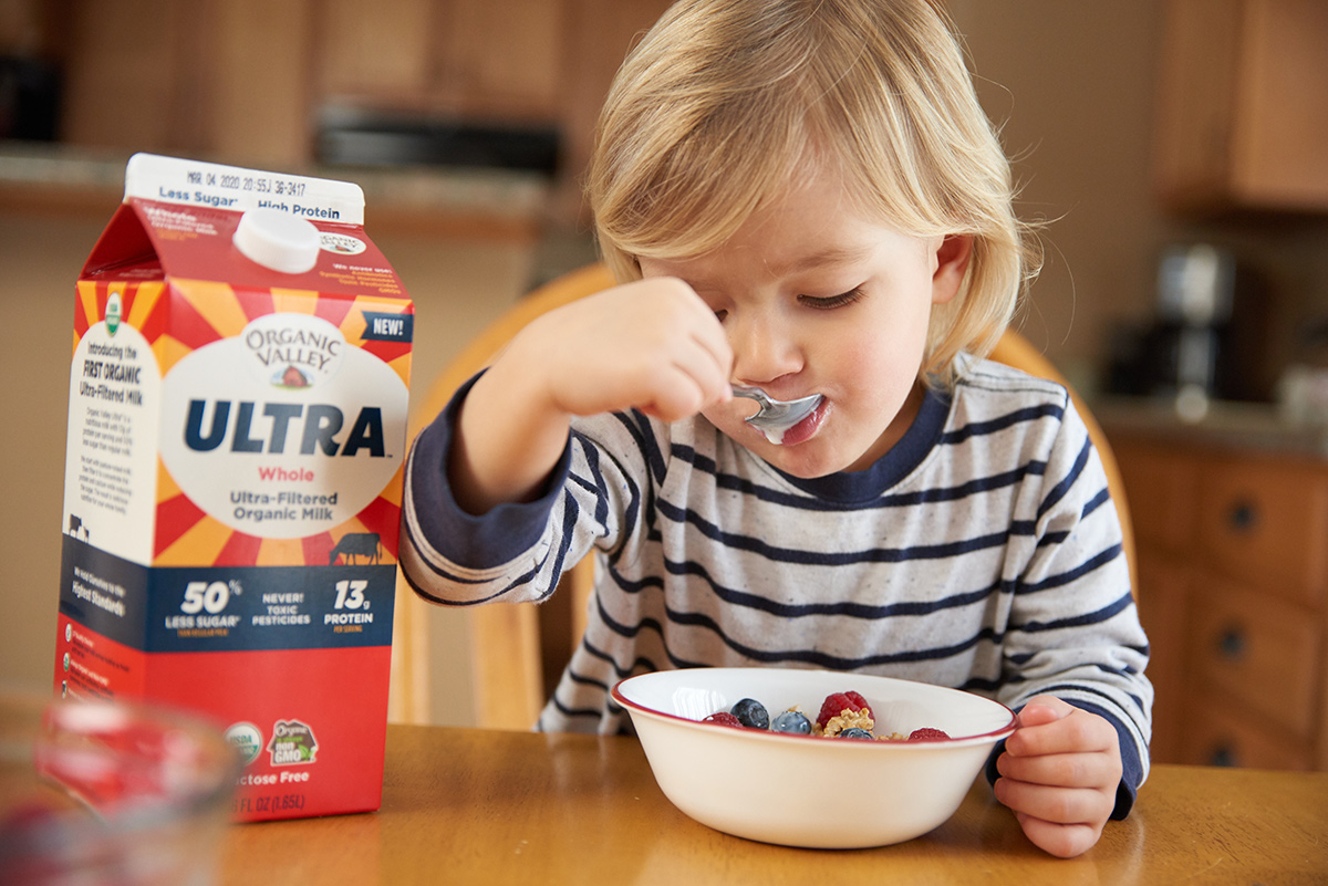 A little boy eats a bowl of cereal with a carton of Organic Valley Ultra milk sitting next to him.