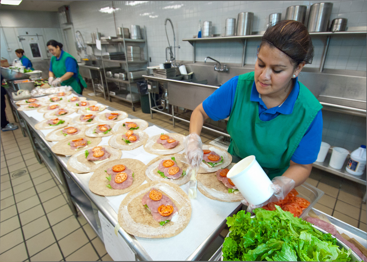A school lunchroom cook spreads mayo onto meat and veggie wraps that she's preparing in the school kitchen.