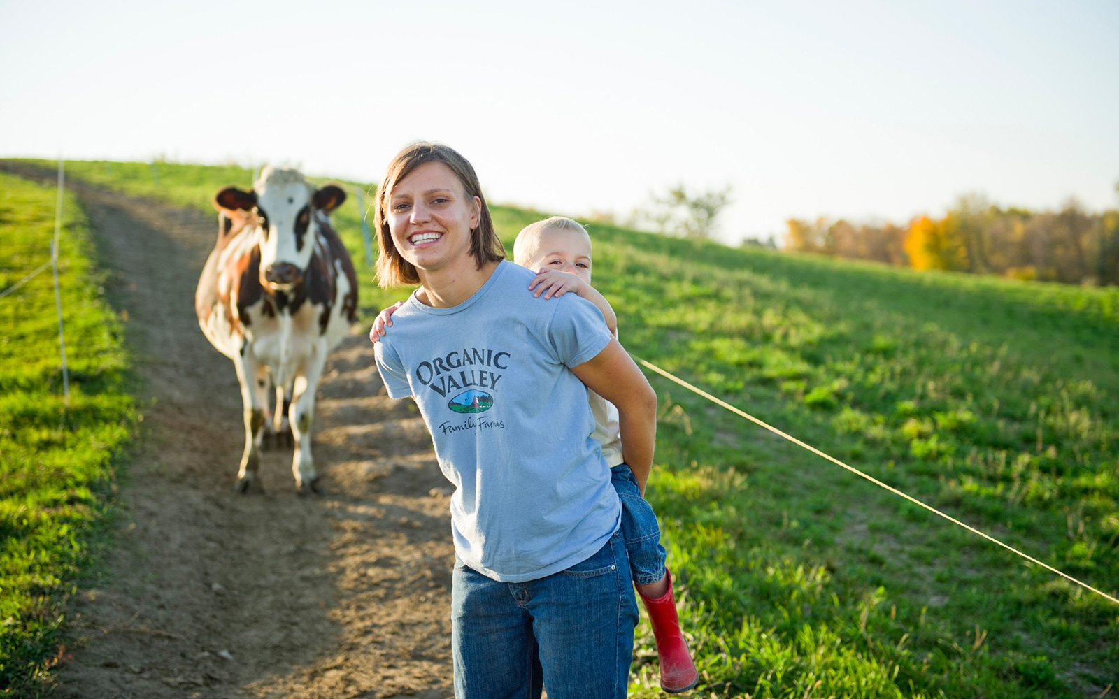 Emily Zweber gives her son a piggyback ride while leading a cow back to the barn.