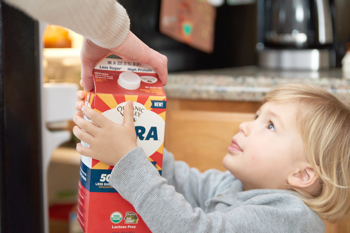 Young boy grabs for a carton of ultra-filtered milk from the fridge.