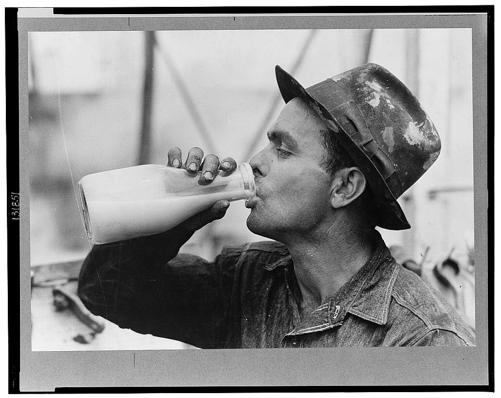 A black and white image of a man drinking from an old fashioned milk bottle.