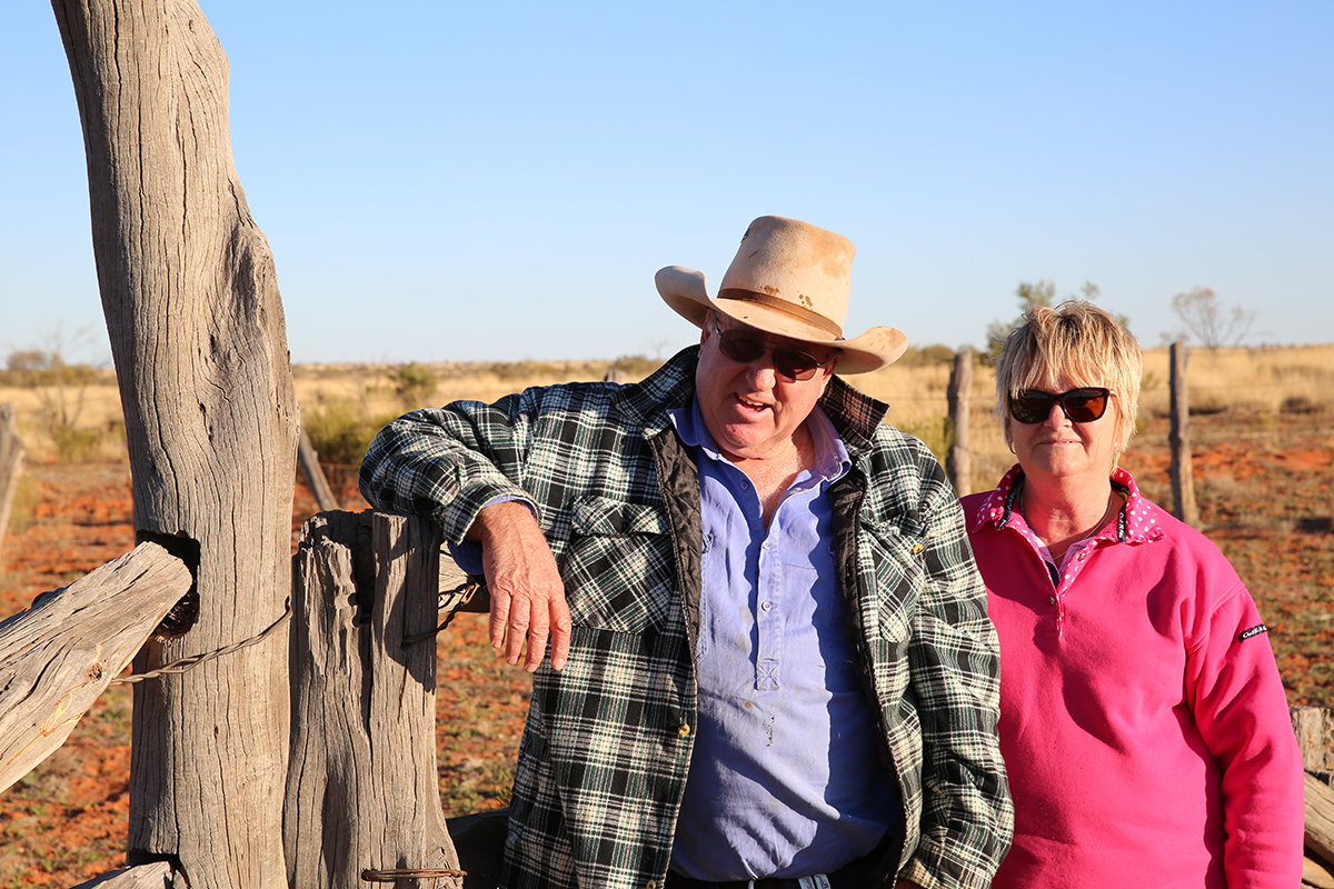 Two Australian grass-fed beef farmers stand in the sun and lean against a wooden post.
